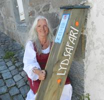 Bilde av Solveig Løvhaug  i middelalderklær med logo til LydSafari på Festningen i Halden i middelalderklær(Foto: Anja Lillerud)